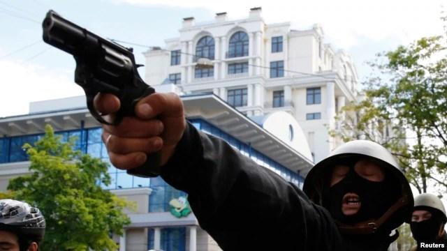 Пророссийский демонстрант целится в сторонников единства Украины во время столкновений в Одессе 2 мая 2014 года