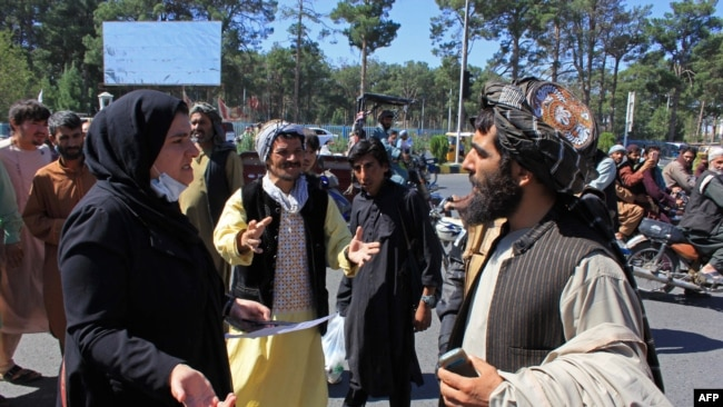 An Afghan woman protester speaks with a member of the Taliban during a protest in Herat on September 2.