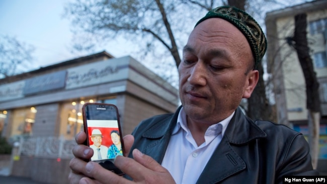 Omirbek Bikaly shows a photo of his parents, whom he believes have been detained in China.