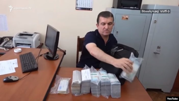 Vachagan Ghazarian empties his bag filled with cash after being arrested by the National Security Service in Yerevan