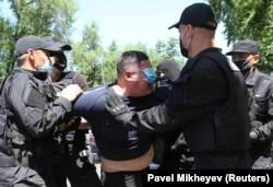 Un hombre que llevaba una mascarilla protectora es detenido durante una manifestación no autorizada celebrada por partidarios de la oposición kazaja en Almaty en junio de 2020.