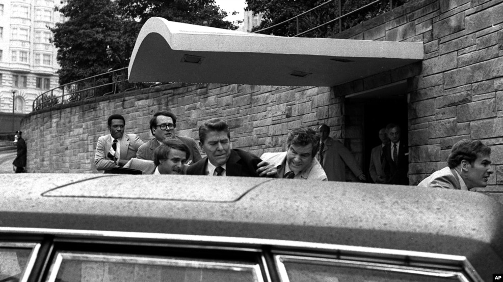 FILE - In this March 30, 1981, photo, U.S. president Ronald Reagan, center, is shown being shoved into his limousine by secret service agents after being shot outside a Washington hotel. The man who shot Reagan is scheduled to leave a Washington mental hospital