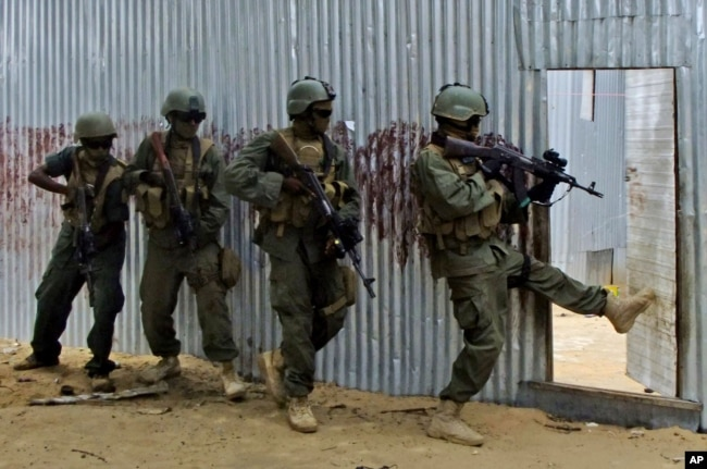 FILE - Somali soldiers search through homes for al-Shabaab fighters, during an operation in Ealsha Biyaha, Somalia, June, 2, 2012.