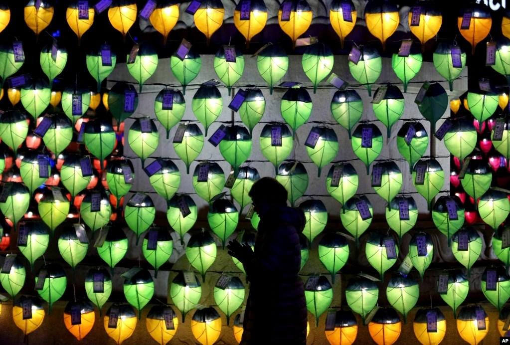 جنوبی کوریا کے دارالحکومت سول کے ایک بودھ مندر میں ایک خاتون نئے سال کے موقع پر جلائی جانے والی لالٹینوں کے سامنے سالِ نو کی عبادت میں مصروف ہے۔