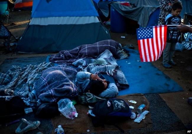 Un migrante que tiene una bandera de los Estados Unidos, a la derecha, habla con otras personas que se despiertan en el Centro Deportivo Benito Juárez que sirve como refugio temporal en Tijuana, México, el lunes 26 de noviembre de 2018.