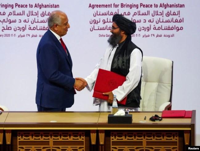 امریکہ اور طالبان کے درمیان امن معاہدے پر دستخطوں کے بعد طالبان وفد کے سربراہ ملا عبدالغنی برادر امریکی نمائںدے زلمے خلیل زاد سے مصافحہ کر رہے ہیں۔ 29 فروری 2020