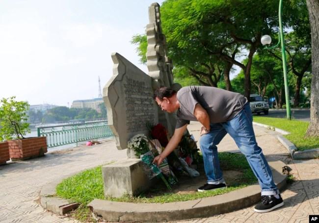Víctor Ramos, un mexicano que ha vivido en California durante los pasados 35 años, coloca flores en el monumento a John McCain en Hanoi, Vietnam, el lunes, 27 de agosto de 2018.