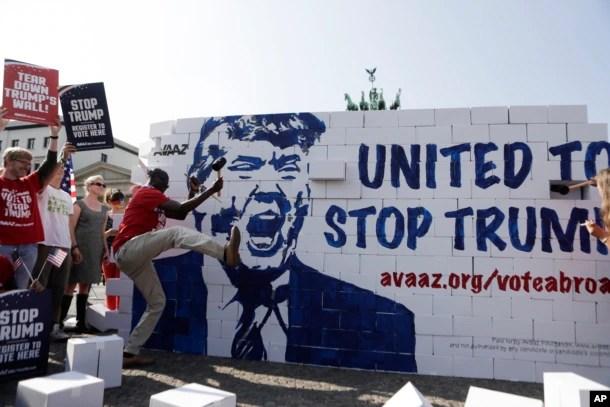 """在德国柏林,反川普示威者捣毁所谓的""""川普仇恨墙"""",标语说,团结起来,阻止川普,选民在此登记"""