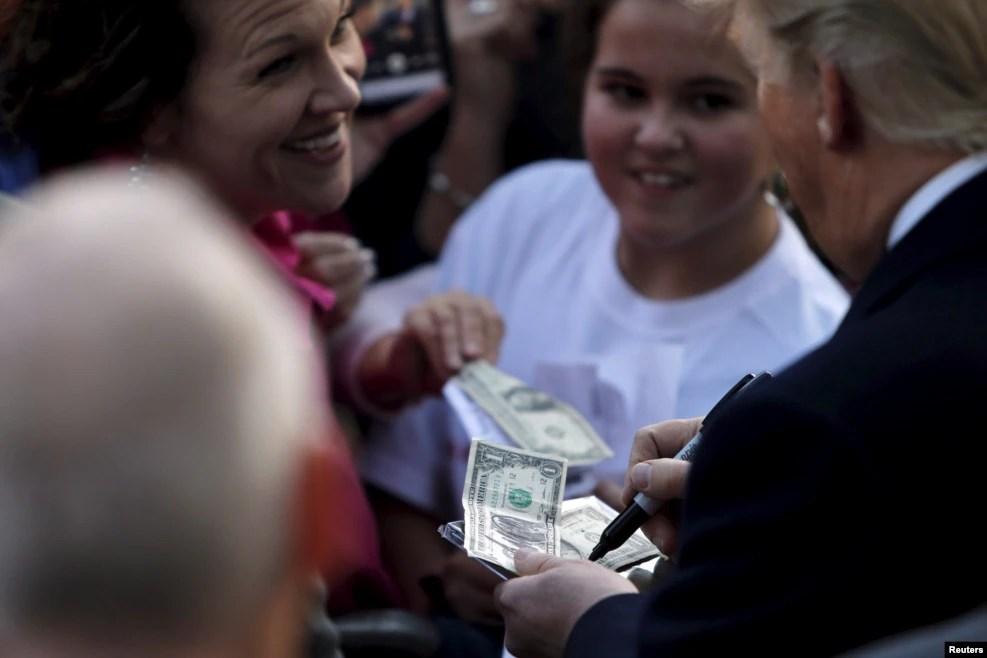 在南卡罗莱纳州,川普在钞票上给黑人支持者签名