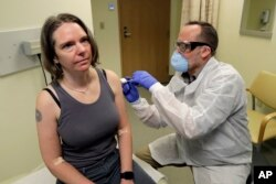 FILE - A pharmacist drops Jennifer Holler, first shot in a first-stage safety study clinical trial of a potential vaccine for COVID-19, disease due to new coronavirus, Monday, March 16, 2020.