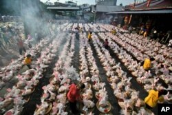 """FILE - Ethnic-Chinese Indonesians arrange offerings for their ancestors' souls during the """"hungry ghost"""" festival in Medan, North Sumatra, Indonesia, Aug. 10, 2014."""
