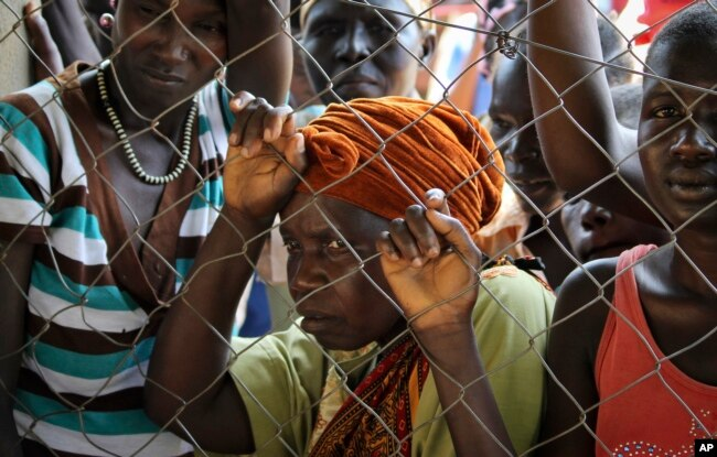 FILE - Women stand outside a U.N. Refugee Agency (UNHCR) site distributing soap, blankets and other items in Yei, in southern South Sudan, Nov. 14, 2016.