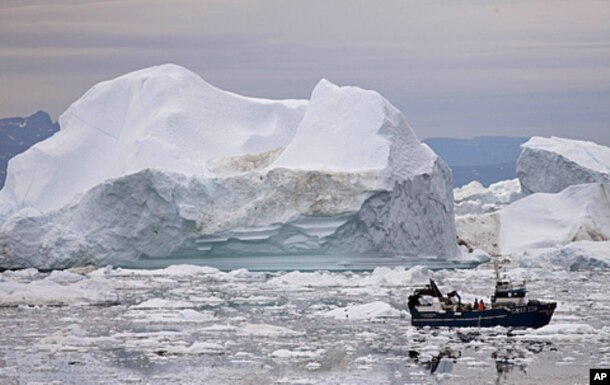FILE - A fishing boat weaves through icebergs shed from the Greenland ice sheet, near Ilulissat, Greenland, July 18, 2011.