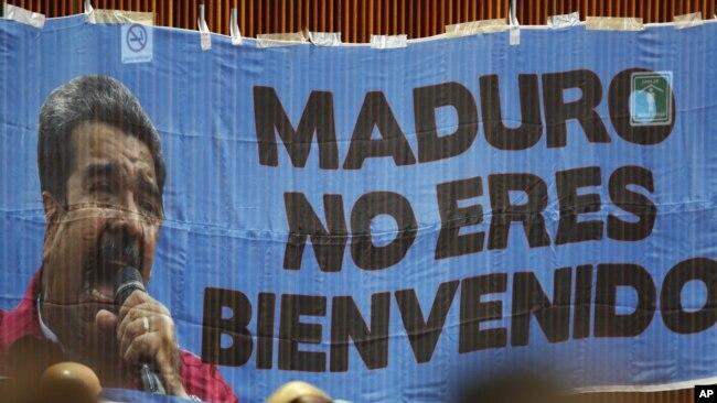 """Legisladores conservadores mexicanos colocaron una manta con la leyenda """"Maduro no eres bienvenido"""" en una pared de la Cámara de Diputados en ceremonia de toma de protesta del izquierdista Andrés Manuel López Obrador como nuevo presidente de México, a la cual fue invitado el mandatario venezolano Nicolás Maduro. (AP Foto/Eduardo Verdugo)"""