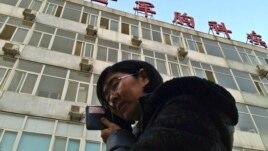 Luật sư của bà Tào Thuận Lợi nói chuyện điện thoại bên ngoài bệnh viện nơi bà Tào đang được chữa trị các chứng bệnh lao phổi và bệnh gan. Những người bạn của bà Tào e rằng bà sẽ qua đời trong nay mai.