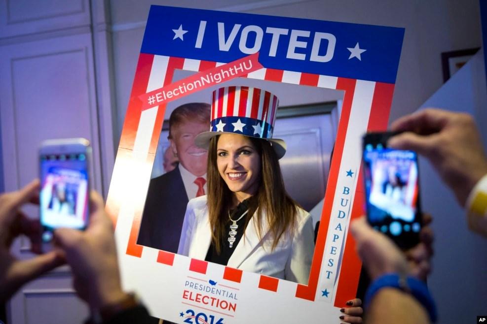 """在美国驻匈牙利使馆,一位女士在川普的纸板像旁边照相,周边的框子上写着""""我投票了""""(2016年11月8日)"""
