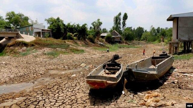 Hai chiếc xuồng nằm trên mặt đất nứt nẻ trong một vùng khô hạn tại tỉnh Cà Mau, Việt Nam. Việt Nam đang đối mặt với đợt hạn hán nghiêm trọng nhất trong 90 năm qua, theo một tuyên bố của Bộ Nông nghiệp và Phát triển Nông thôn.