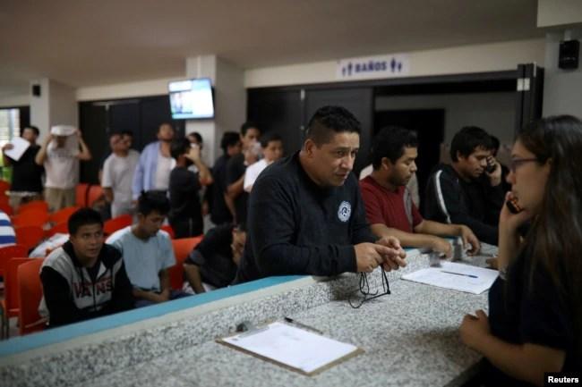 ARCHIVO- Personas deportadas de Estados Unidos esperan para hacer una llamada telefónica a EE.UU. en una instalación de inmigración en San Salvador, El Salvador, el 3 de julio de 2018.