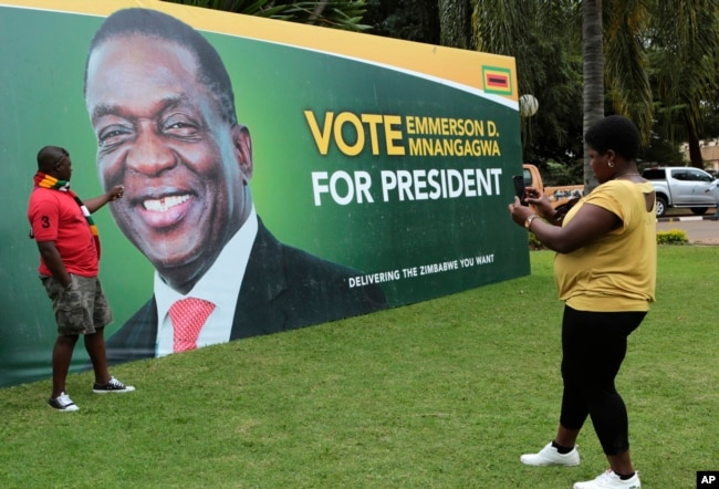 FILE - A man has his picture taken in front of an election campaign poster of Zimbabwe President Emmerson Mnangagwa portrait, in Harare, May, 4, 2018.