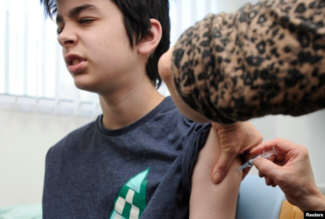Seorang anak remaja diberi suntikan vaksin MMR di sekolah di Swansea, Wales selatan, Inggris. (Reuters)