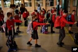 Sekelompok siswa muda yang mengenakan masker sedang mengantri dan menerapkan jarak sosial sebelum memasuki ruang kelas, di sekolah Luis Amigo, di Pamplona, Spanyol utara, 7 September 2020. (Foto: AP)