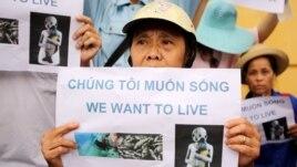 """Một người phụ nữ cầm tấm bảng với nội dung """"Chúng tôi muốn sống"""" trong cuộc biểu tình về vụ cá chết hàng loạt ở miền trung Việt Nam, ngày 1 tháng 5 năm 2016."""