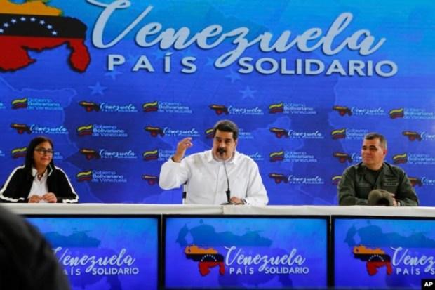 El presidente de Venezuela, Nicolás Maduro, en el centro, habla, mientras lo acompaña el vicepresidente venezolano, Delcy Rodríguez, a la izquierda, y el ministro de Defensa, Vladimir Padrino, a la derecha, durante una reunión con ciudadanos colombianos que residen en Venezuela. Caracas, 26 de septiembre de 2018. Foto de la oficina de prensa del Palacio de Miraflores via AP.