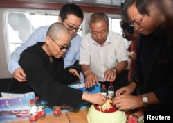 FILE - Liu Xia, wife of deceased Chinese Nobel Peace Prize-winning dissident Liu Xiaobo and other relatives attend his sea burial off the coast of Dalian, China, in this photo released by Shenyang Municipal Information Office July 15, 2017.