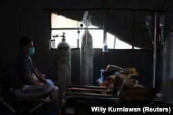Seorang pasien COVID-19 duduk di atas velbed di tenda sementara di luar ruang gawat darurat rumah sakit pemerintah di Bekasi, 25 Juni 2021. (Foto: REUTERS/Willy Kurniawan)