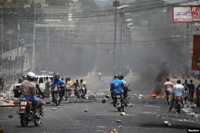 Haitianos atraviesan una barricada en una calle de Puerto Príncipe, Haití, el 8 de julio de 2018. Reuters.