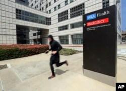 Seorang pria berlari melintas di depan gedung Ronald Reagan UCLA Medical Center di kampus Universitas California, Los Angeles, 26 April 2019. (Foto: AP)