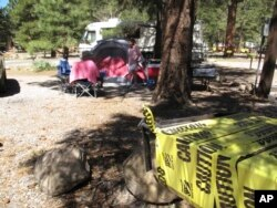 Los Angeles residents John and Pauline Barba tidy up their campsite in Flagstaff, Ariz., May 24, 2016. The charcoal grills were off-limits because of extreme fire danger, and portions of the nearby national forest closed.