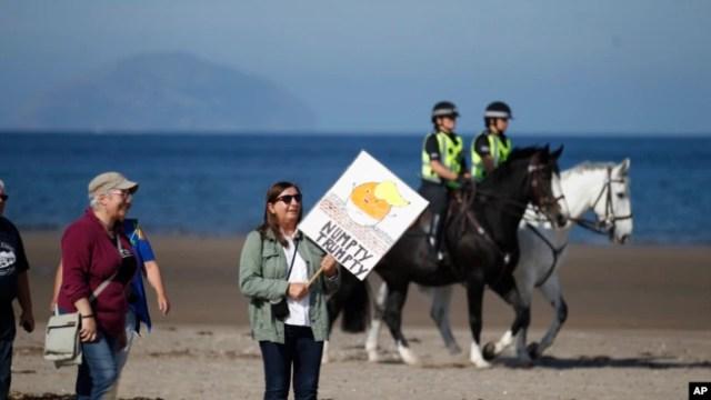 Manifestantes llegan el sábado a la playa cerca al club de golf de Trump en Tumberry, Escocia.