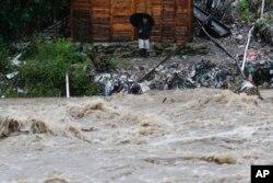 Seorang pria menyaksikan naiknya air di Rio Bermejo, San Pedro Sula, Honduras, pasca hantaman Badai Iota, Selasa, 17 November 2020.