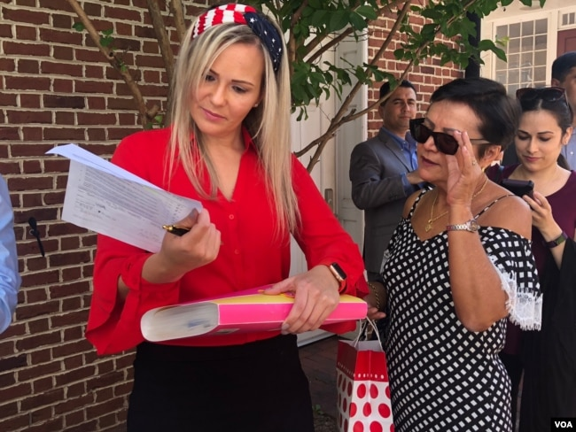 Kelly Oliveira examines paperwork before her naturalization ceremony in Baltimore, Maryland. (Photo: A. Barros / VOA)