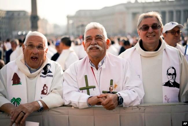 Sacerdotes vestidos con la imagen del asesinado arzobispo salvadoreño Oscar Romero asisten a una ceremonia de canonización en la Plaza de San Pedro en el Vaticano, 14 de octubre de 2018.