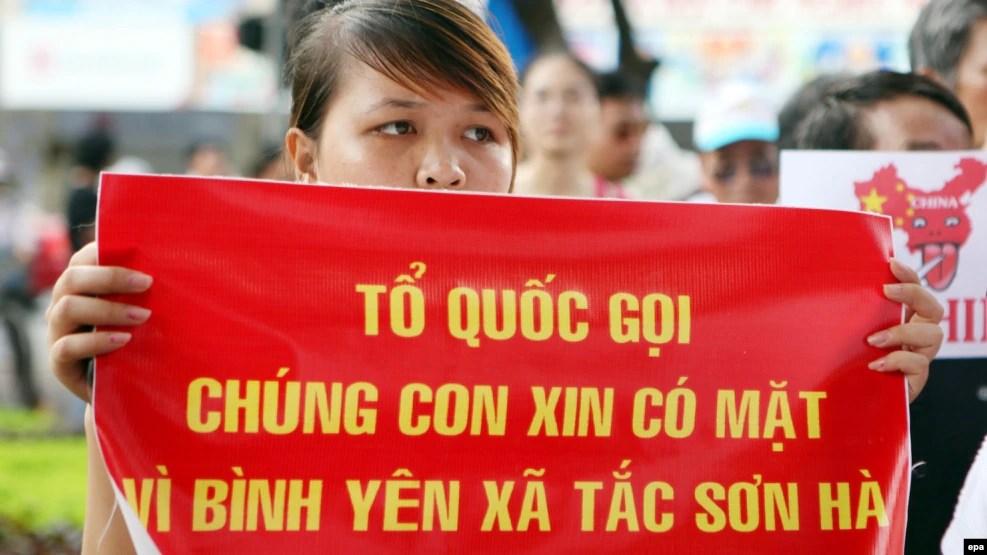 Người phụ nữ cầm biểu ngữ tại một cuộc biểu tình phản đối Trung Quốc ở Hà Nội, ngày 14/8/2011.