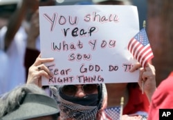A demonstrator holds a sign during a protest outside the U.S. Border Patrol Central Processing Center, in McAllen, Texas, June 23, 2018.