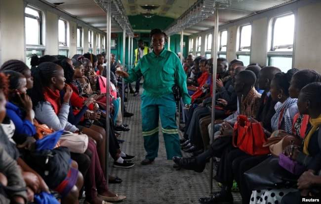 FILE - A train conductor walks inside a carriage as passengers ride inside a Nairobi Commuter Rail Service train from the Mutindwa station in Nairobi, Kenya, Nov. 12, 2018.