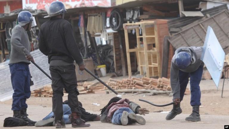 FILE: Armed Zimbabwean police beat up alleged rioters in Harare, Monday, July, 6, 2016. (AP Photo/Tsvangirayi Mukwazhi)