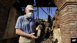 Dario Sattui holds one of the more than 100,000 bottles of wine lost when fire devoured a building near his Tuscan-style castle, Castello di Amorosa in Calistoga, Calif., on Thursday, Oct. 15, 2020. (AP Photo/Eric Risberg)