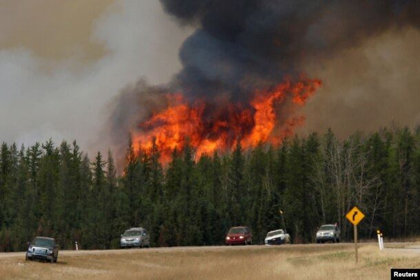 A wildfire burns as evacuees who were stranded north of Fort McMurray, Alberta, Canada head south of Fort McMurray on Highway 63, May 6, 2016.