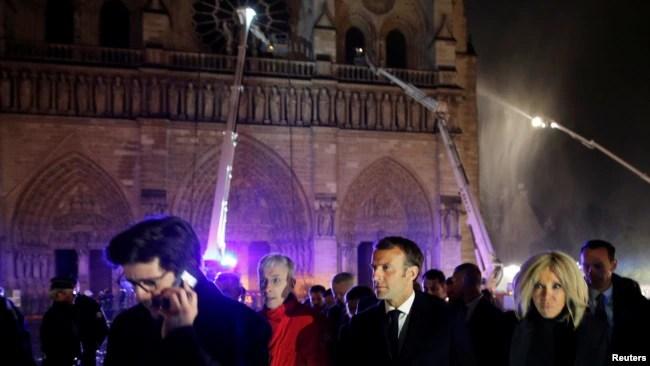 El presidente francés Emmanuel Macron y su esposa Brigitte a las afuera de Notre Dame mientras bomberos intentan contener el fuego. Photo: Reuters.