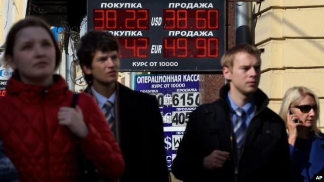 Cư dân đi bộ qua quầy đổi tiền ở Moscow. Đồng rúp của Nga tiếp tục mất giá so với đồng Euro và Đôla.