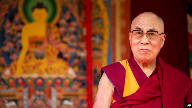 FILE - Tibet's exiled government and Buddhist spiritual leader, the Dalai Lama, on stage before making a speech at the ESS Stadium in Aldershot, southern England, June 29, 2015.