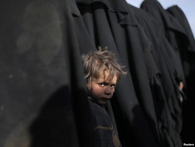 A boy looks at the camera near Baghuz, Deir el-Zour province, Syria, March 5, 2019.