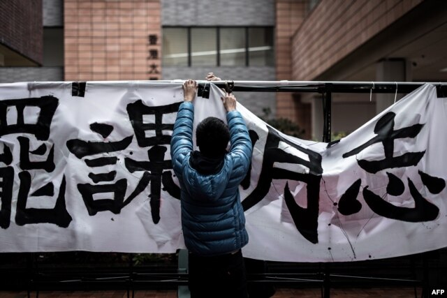 FILE - A student sets up a banner during a protest at the campus of Hong Kong's leading university HKU in Hong Kong on January 20, 2016.