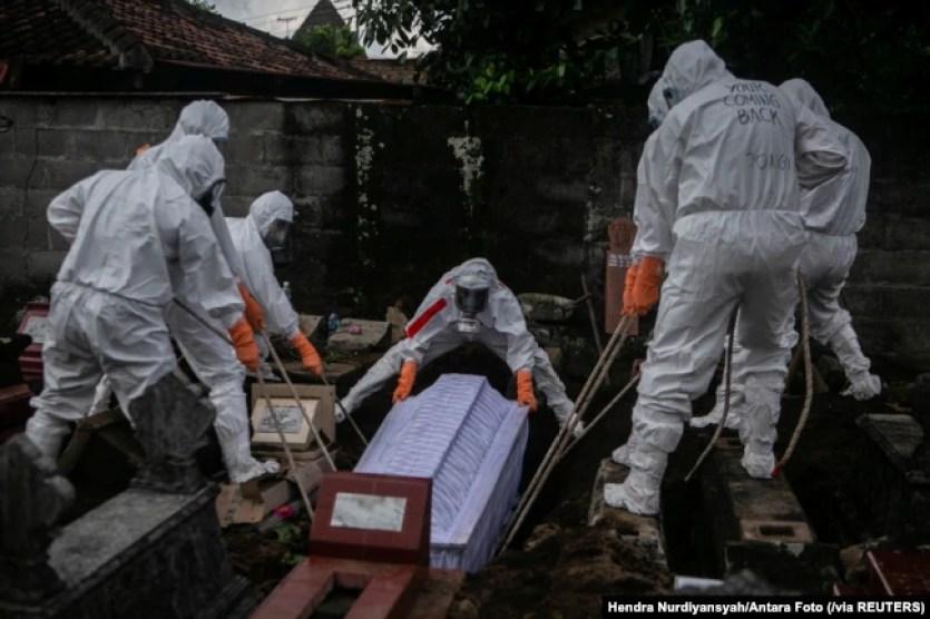 Para pegawai dinas pemakaman dengan mengenakan alat pelindung diri (APD) sedang memakamkan jenazah pasien COVID-19 di tempat pemakaman umum di Badran, Yogyakarta, 22 Juni 2021. (Foto: Hendra Nurdiyansyah/Antara Foto via Reuters)