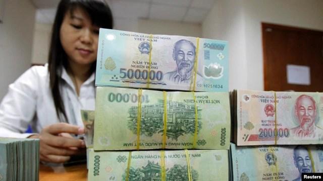 Nhân viên đếm tiền tại quầy của Ngân hàng Quốc tế Việt Nam ở Hà Nội.