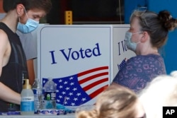 A voter fills out his ballot as a woman waits her turn during primary voting at the public safety building in McKeesport, Pa., Tuesday, June 2, 2020. (AP Photo/Gene J. Puskar)